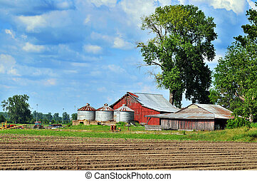 Country barn with silos during a sunny day