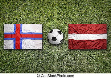 Faroe Islands vs. Latvia flags on soccer field