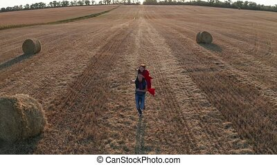 Farther running across field with son on shoulders