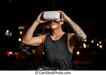 Fascinated muscular and tattooed man in night vision glasses