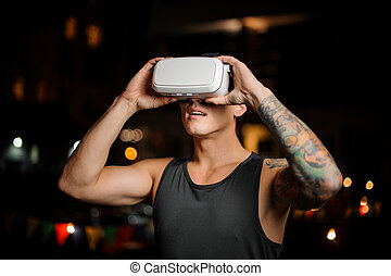 Fascinated muscular and tattooed young man in night vision glasses
