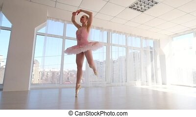 Fascinating female ballet dancer in pink tutu practicing and...