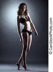 Fascinating leggy girl posing in studio, on gray backdrop
