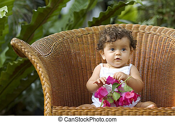 Infant sitting on a big wicker chair playing with an orchid in a tropical garden setting