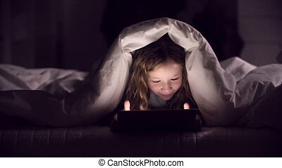 Fascinating Pastime - Girl wrapped in blanket on bed playing...