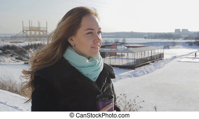 Fascinating woman walks against background of snow-covered landscape.