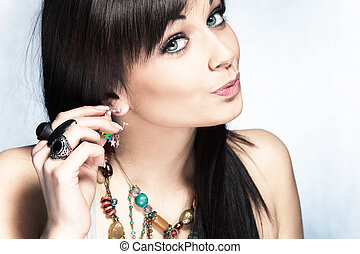 fashion accessories - blue eyes woman put on earring, studio...