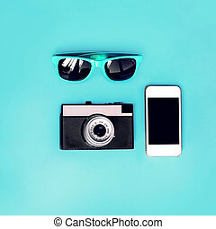 Fashion accessory, sunglasses, vintage camera with a smartphone on a blue background, top view