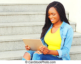 Fashion african woman using tablet pc computer sitting in the city