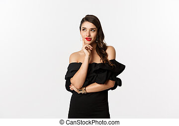 Fashion and beauty. Thoughtful young woman in black dress, smiling pleased and thinking, having an idea, white background