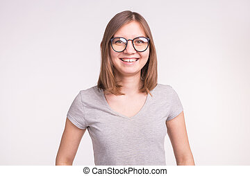 Fashion and people concept - Portrait of young smiling woman in glasses on white background with copy space