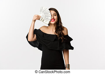 Fashion and shopping concept. Happy young woman in black dress, with red lips, holding money and smiling satisfied, standing over white background