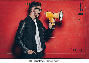 Fashion announcement. Side view of handsome young man in sunglasses holding megaphone and keeping mouth open while standing against red background