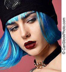 young grunge style woman with blue wig hair in gold chain choker on neck and black hat