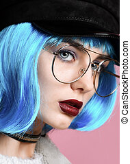 Fashion art photo of young grunge style woman with blue wig hair in gold chain choker on neck black leather hat and clear sunglasses