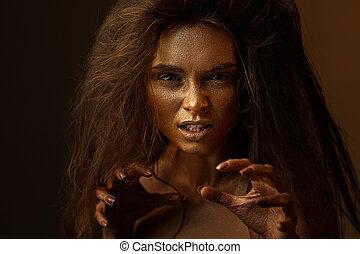 beaty woman with gold metallic body and hair on dark ...