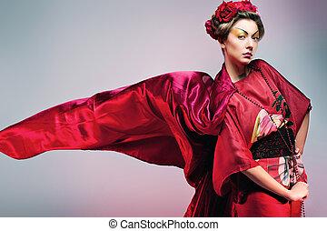Fashion asian woman wearing traditional japanese red kimono, studio shot. Geisha