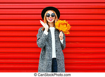 Fashion autumn cheerful woman with yellow maple leaves on red background