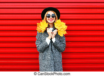 Fashion autumn happy smiling woman holds yellow maple leaves on a red background