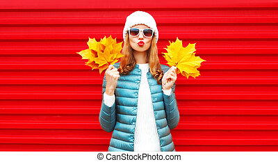 Fashion autumn portrait woman holds yellow maple leaves, blows red lips, sends an air kiss on background in city