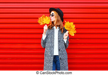 Fashion autumn pretty woman with yellow maple leaves, wearing a coat on red background