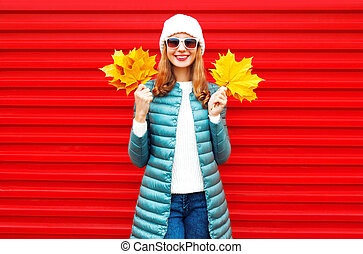Fashion autumn smiling woman holds a yellow maple leaves in hands on red background in the city