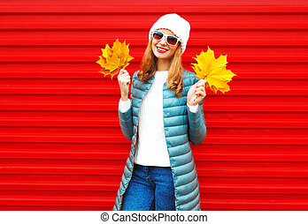 Fashion autumn smiling woman holds yellow maple leaves in hands on a red background in the city