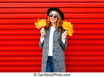 Fashion autumn smiling woman holds yellow maple leaves on a red background
