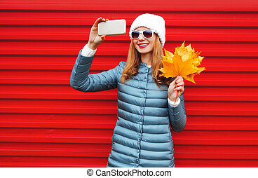 Fashion autumn smiling woman takes a picture self portrait on a smartphone with yellow maple leaves over colorful red background