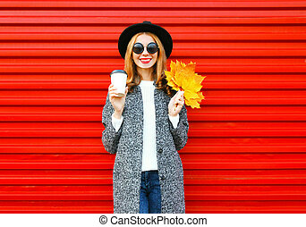 Fashion autumn smiling woman with coffee cup and yellow maple leaves on red background