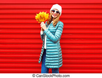 Fashion autumn smiling woman with yellow maple leaves in hands on a red background
