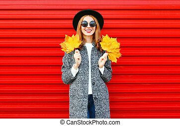 Fashion autumn smiling woman with yellow maple leaves on a red background