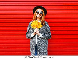 Fashion autumn smiling woman with yellow maple leaves on colorful red background