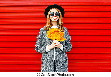Fashion autumn smiling woman with yellow maple leaves on red background