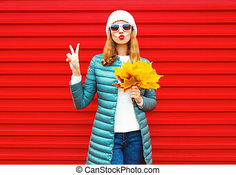 Fashion autumn woman holds yellow maple leaves, blows red lips, sends an air kiss on background in city
