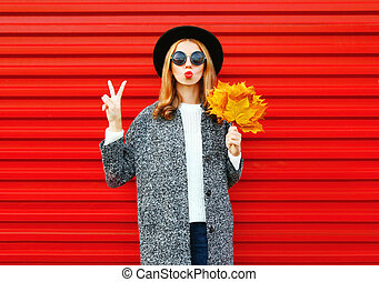 Fashion autumn young woman with red lips and yellow maple leaves on a background