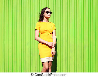 Fashion beautiful young woman in yellow dress and sunglasses against the colorful green background