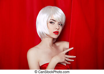 Fashion Beauty Blond Portrait with White Short Hair. Make-up. Beautiful Girl Face Close-up. Hairstyle. Fringe. Vogue Style Woman isolated on curtain or drapes red background.