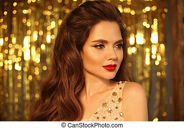 Fashion Beauty Girl Portrait Isolated on golden Christmas glittering bokeh lights background. Glamour Makeup. Gold Jewelry. Hairstyle. Alluring brunette with sensual red lipstick looking at camera