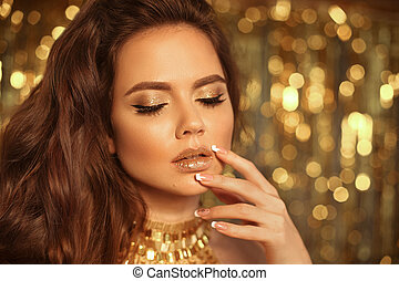 Fashion Beauty Girl Portrait Isolated on golden Christmas lights glitter bokeh background. Glamour Makeup. Gold Jewelry. Hairstyle. Alluring brunette with glittering lipstick and manicured nails