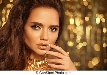 Fashion Beauty Girl Portrait Isolated on golden Christmas lights glitter bokeh background. Glamour Makeup. Gold Jewelry. Hairstyle. Alluring brunette with glittering lipstick and manicured nails.