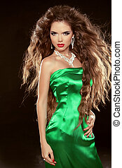 Fashion Beauty Girl with long brown blowing hair posing in elegant dress isolated on black background