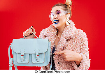 Fashion blogger feeling satisfied getting her blue leather bag