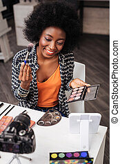 Pretty dark-skinned woman with coral lipstick holding blusher palette