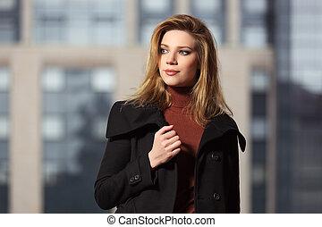 Fashion blond woman in black coat walking on the city street