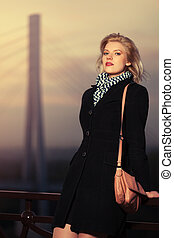 Fashion blond woman in black coat with handbag leaning on fence outdoor