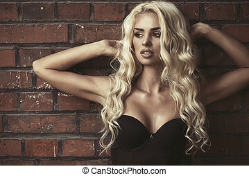 Fashion blond woman over brick wall