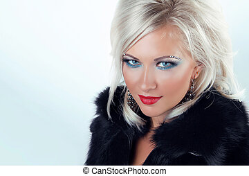 Fashion blond woman with blue eyes and red lips, wearing in fur coat