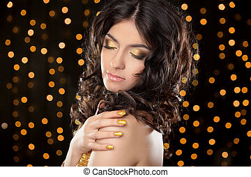 Fashion brunette girl with Long curly hair, beauty makeup, luxury jewelry. Beautiful attractive young woman in golden dress posing over holiday lights glitter background.
