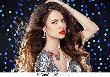 Fashion brunette girl with long wavy hair, beauty makeup, luxury jewelry. Beautiful attractive young woman in dress of sequin posing over holiday lights background.